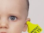 2000/11/15:Germany/Deutschland - Baby mit Patentclip im Ohr. Symbol fuer Patente auf Leben.  Baby with patent clip in the ear. Symbol for patents on life.     ©Axel Kirchhof/Greenpeace (Montag - 0012201 - (×××)